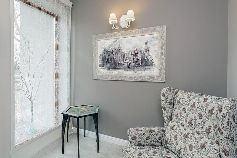 Картина с пейзажем в интерьере комнаты