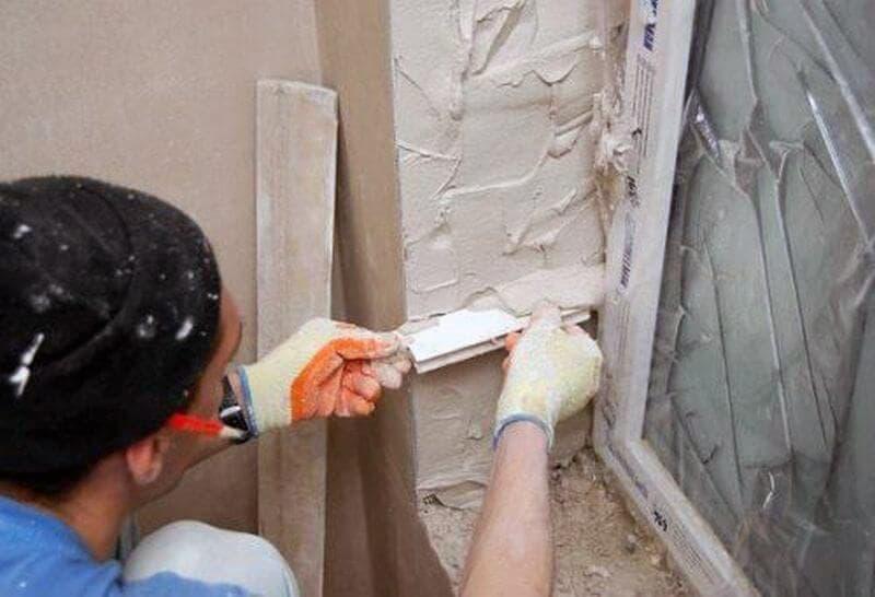 Процесс оштукатуривания откоса окна