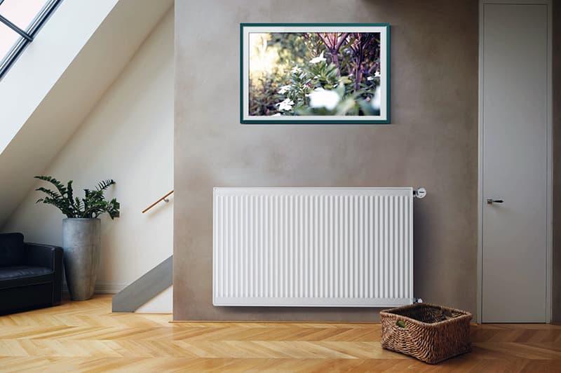 Стальной радиатор в интерьере комнаты