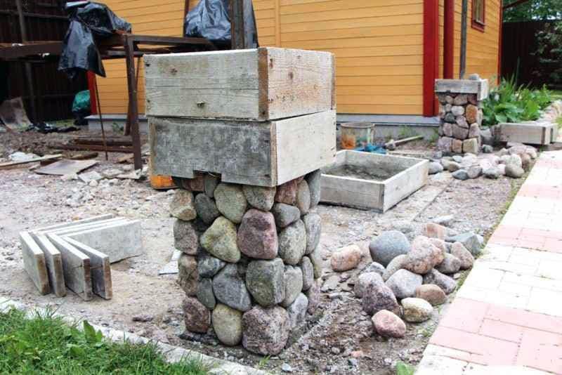 Процесс заполнения столбов при возведении забора из камня