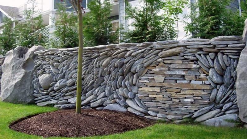 Создание композиций на заборе из камня