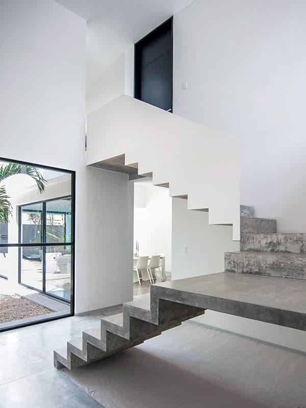 Угловая лестница из бетона в доме