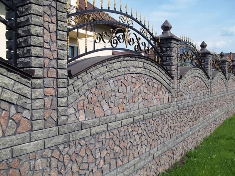 Украшение забора из камня коваными элементами