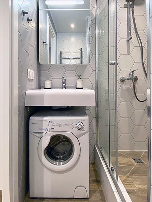Пральна машина під навісним умивальником у ванній кімнаті